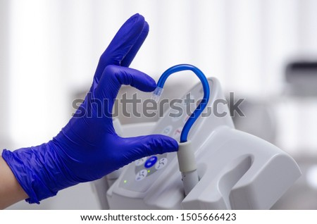 Photo of  Saliva ejector and a hand in a disposable glove symbolize love in dentistry.Hand in a blue glove.Blue saliva ejector.The atmosphere of the dental office.With love in dentistry.Heart symbol.