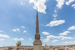 Sallustiano Obelisk against blue sky above Spanish Steps, in front of The church of the Santissima Trinità dei Monti in Rome, Italy