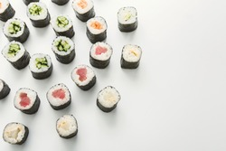 Salmon and cucumber sushi rolls. Asian food restaurant delivery, top view on platter set, white background, copy space