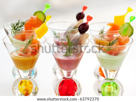 Salmon and herring appetizers in glasses with three different  sauce(mustard,wasabi and cranberry sauce)