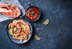 Salmon and shrimps on plate with lemon, salt, sauce. Background. Fish and seafood. Top view. Big red prawns and salmon for lunch/dinner on rustic stone table. Healthy clean eating/diet. Space for text