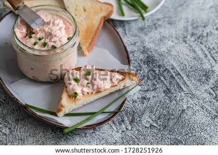 Salmon and soft creme cheese spread in jar. Salmon rillettes, mousse, pate and toasts on gray background