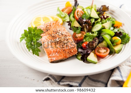 Stock Photo Salmon Baked and Served with Tomatoes, Cucumbers, Avocado, Greens