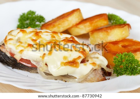 Salmon baked under vegetables and mayonnaise with potatoes