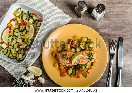 Salmon baked with thyme and Mediterranean vegetables on wood table with plate
