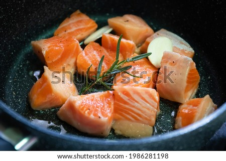 Salmon Belly or Salmon Toro sliced with rosemary and garlic cooking on pan. Foto stock ©