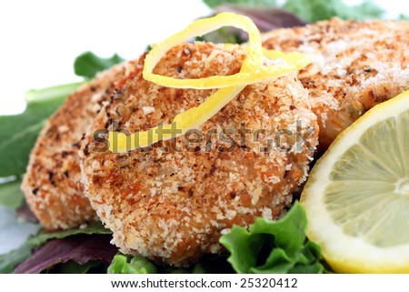 Salmon cakes on bed of lettuce with lemon