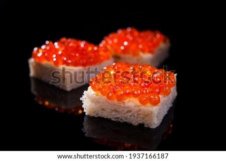 salmon caviar on a piece of white kanape bread on a black background Stock fotó ©