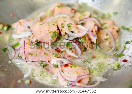 Salmon ceviche being marinated in stainless steel pot