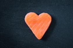 Salmon fillet copy space black slate background, healthy eating omega 3 concept. Heart shaped salmon steak.