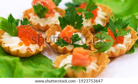 Salmon fillet mini tartlet with cream, garnished with red salmon caviar on a white plate with herbs on the table Side view Stock fotó ©