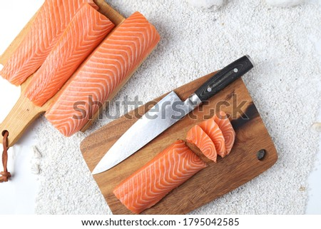Salmon fillet on a wooden cutting board is sashimi, stone background. Foto d'archivio ©