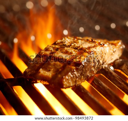 salmon fillet on the grill with flames closeup