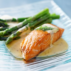 Salmon fillet with asparagus and yellow sauce closeup