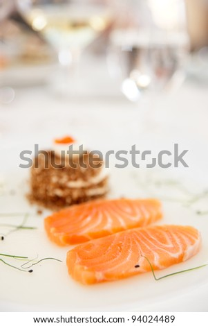 Salmon fillet with bread and caviar on restaurant table