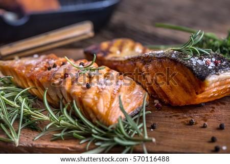 Shutterstock Salmon fillets. Grilled salmon, sesame seeds herb decorationon on vintage pan or black slate board. fish roasted on an old wooden table.Studio shot.