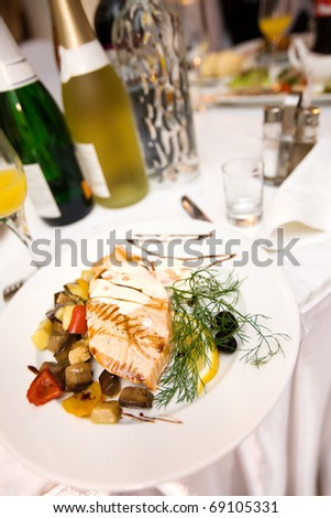 Salmon fish dish decorated on white plate in restaurant
