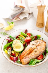 Salmon fish steak grilled, avocado and fresh vegetable salad with tomato, bell pepper and leafy vegetables.