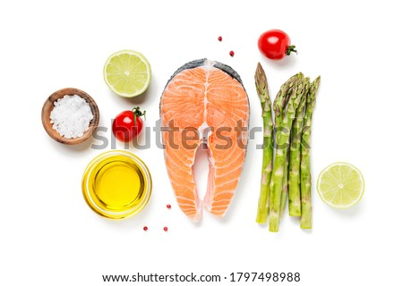 Salmon fish. Uncooked salmon steak with ingredients for cooking - fresh asparagus and spices isolated  on white background