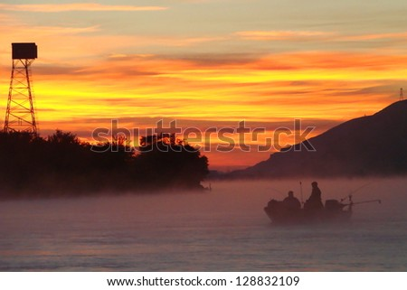 Salmon fishing boat on the Columbia River at sunrise in morning fog, Washington state trout fly fishing trolling motor boat Pacific Northwest foggy mist silhouette