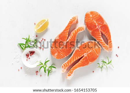 Salmon. Fresh raw salmon fish steaks with cooking ingredients, herbs and lemon on white background, top view