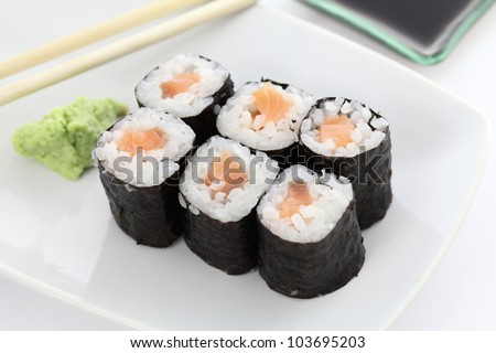 Salmon Maki sushi with chopsticks and soy sauce in white background