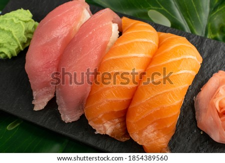 Salmon nigiri sushi and maguro tuna susi set on green palm leaf. Macro photo of susi set rolls with raw red fish on dark stone plate close up Stok fotoğraf ©