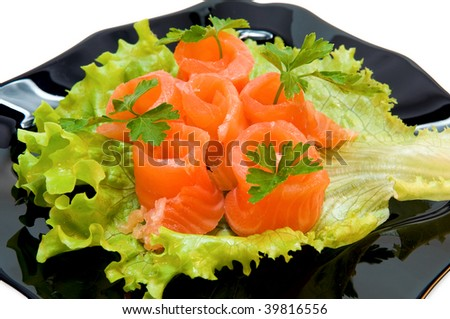 Salmon on a green sheet in a black dish, it is isolated