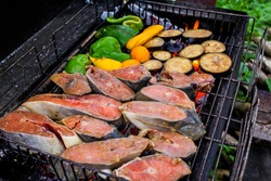 Salmon or trout red fish fillet on grill (bbq, barbecue) cooked on fire. Seafood steak filet roast for dinner on charcoal. Fish (salmon or trout) bbq grill roast. Staycation picnic with fish grill bbq