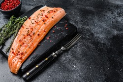 Salmon or trout sea fish fillet with salt and pink pepper. Black wooden background. Top view. Copy space