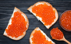 Salmon Red Caviar. Red fish caviar on a spoon in glass bowl. Sandwich with white bread, butter and red caviar. Raw seafood. Luxury delicacy food. Dark natural wooden background. Flat lay, top view.