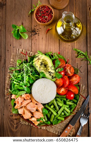 Salmon, rice, tomatoes, avocado, mix salad, green beans in buddha bowl on a wooden table. Delicious balanced food concept