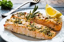 Salmon roasted in an oven with a butter, parsley and garlic. Portion of cooked fish and fresh lemon on a white plate on the wooden table