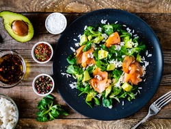 Salmon salad - smoked salmon white rice and vegetables on wooden table