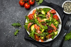 Salmon salad with green leaves, avocado and tomato on black stone background. Top view with copy space.