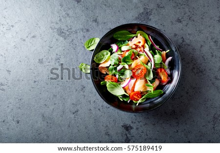 Salmon Salad with spinach, cherry tomatoes, corn salad, baby spinach, fresh mint and basil. Home made food. Concept for a tasty and healthy meal. Dark stone background. Top view. Copy space.