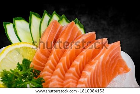 salmon sashimi with black background. Japanse cuisine. Sushi on a black table. Foto d'archivio ©