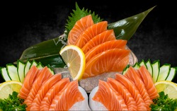 salmon sashimi with black background. Japanse cuisine. Sushi on a black table. A variety of Japanese food, appetizing menu. low lighting.
