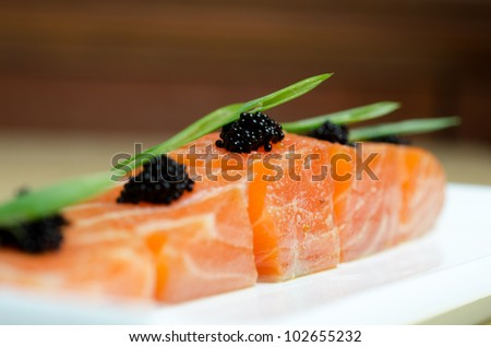 Salmon Slices with black tobiko caviar and greens