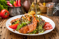 Salmon steak in white dish with vegetables on the table
