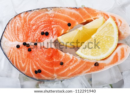 salmon steak with slices of lemon and black pepper on the ice