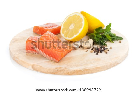 Salmon steaks on cutting board with lemons and herbs. Isolated on white background