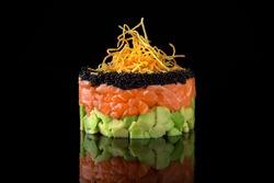 Salmon tartare with avocado and caviar on a black background. Sushi menu. Japanese food
