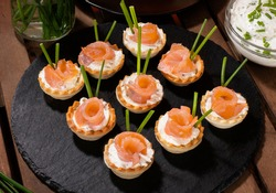 salmon tartlets with cheese and chives on the table with ingredients