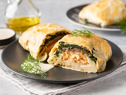 Salmon Wellington with spinach and mushrooms (champignons) baked in puff pastry served with creamy sauce and green dill on black ceramic plate. Homemade tasty pie. Traditional fish dish. Close up view