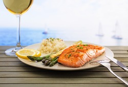 Salmon with asparagus and rice. Freshly served with a glass of wine and sea view .