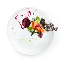 Salmon with caviar, greens and cucumber on creamy sauce and basil leaves on white plate on an isolated background. Gastronomic restaurant menu. Top View