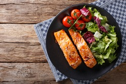 Salmon with sesame seeds in Asian style and fresh salad close-up on a plate. horizontal view from above