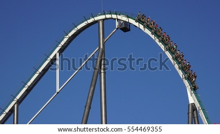 SALOU, SPAIN JULY 5 2016: People On Roller Coaster Thrill Ride on July 5 2016 in Salou, Spain #554469355