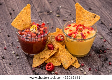 Salsa- and Cheese Sauce with fresh Nachos on wooden background